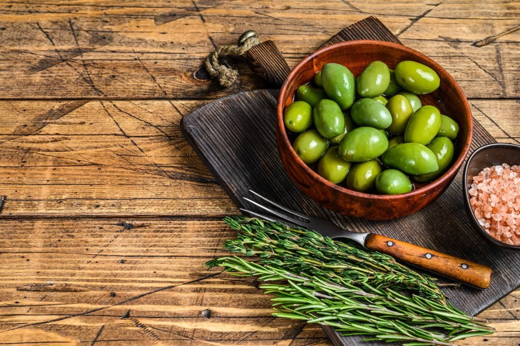 Marinated big green olives in dark wooden bowl with herbs and rosepink himalaya salt as decor