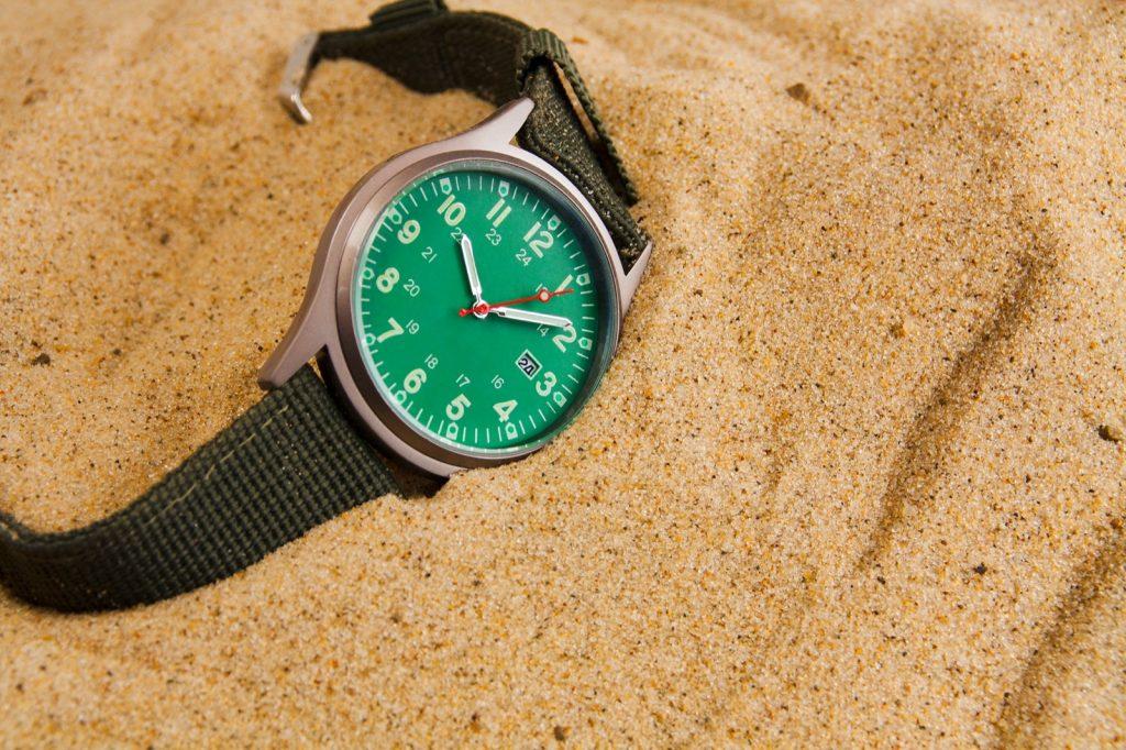 Green watch half buried in sand