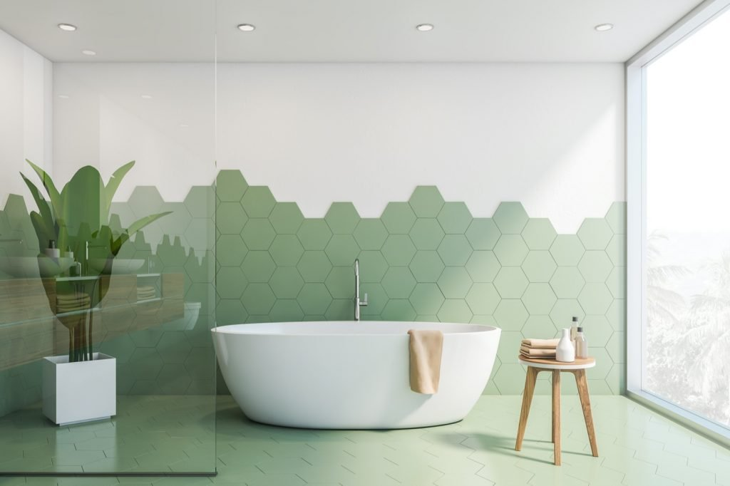 Interior of stylish bathroom with green hexagonal tiles and white walls. White bathtub with towel on it.