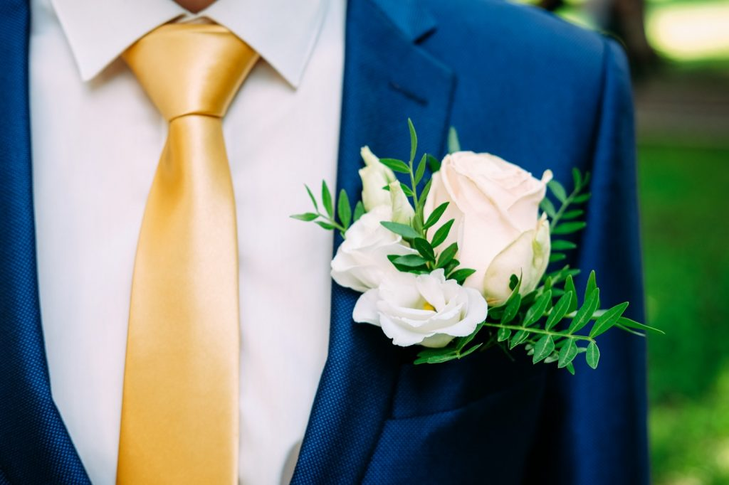 Groom in dark blue suit and yellow necktie wearing a white rose buttonhole bouquet