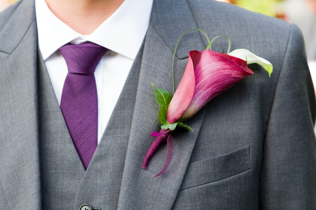 Groom wearing a purple tie and a calla lily buttonhole flower