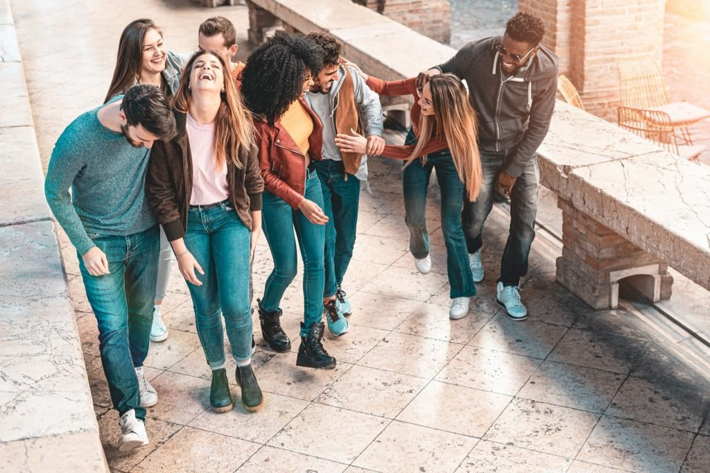 Group of young people in teal colored clothes smiling having fun walking together outdoors in the street