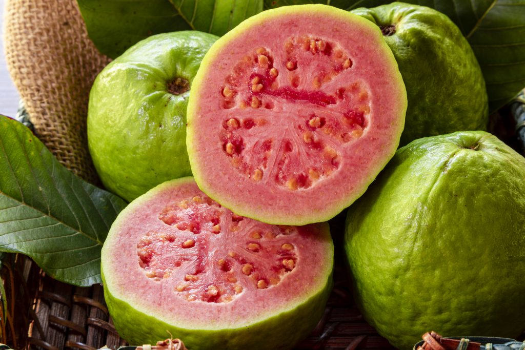 Close up of a bunch of guavas in a basket, one of them is cut in half