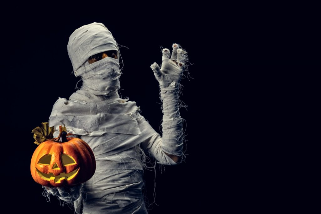 Ancient mummy posing with orange pumpkin on black background