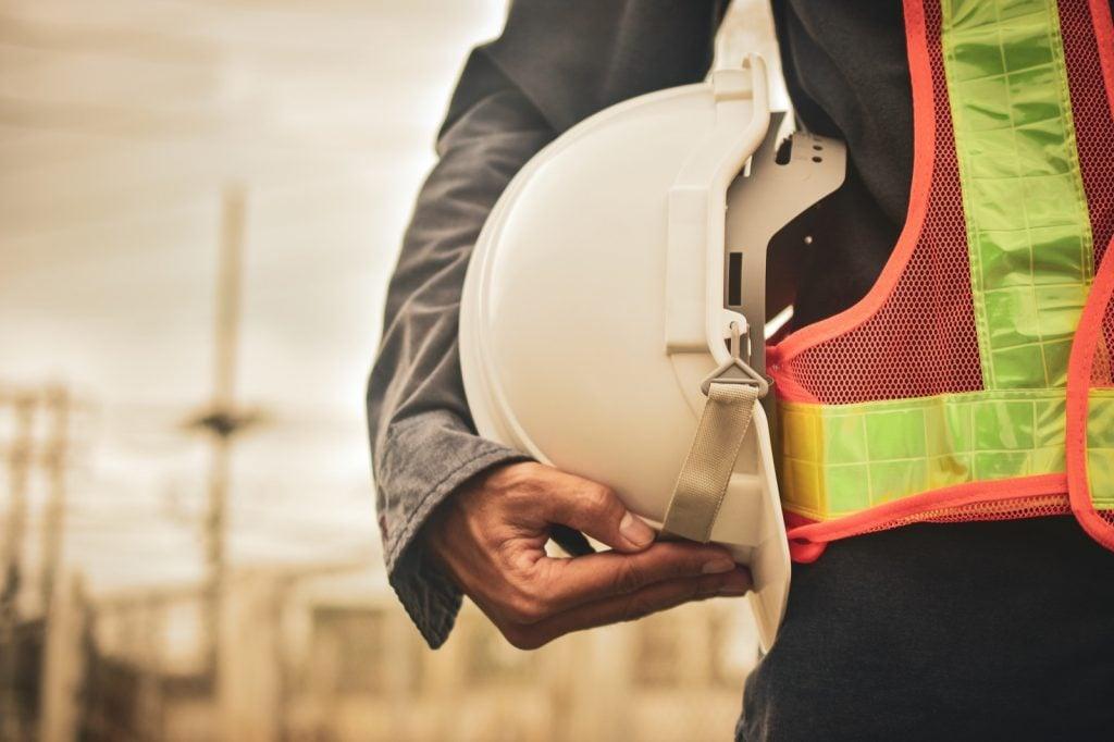 Worker holding white hard hat helmet in hand