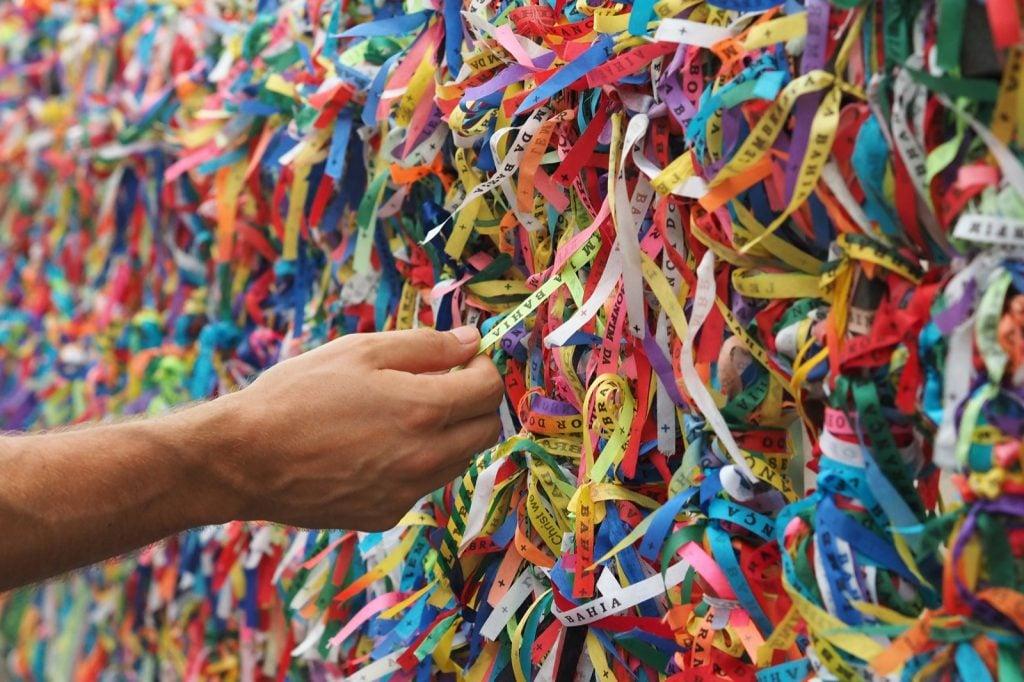 Hand touching colorful Senhor do Bonfim ribbons at Pelourinho in Salvador, Bahia, Brazil