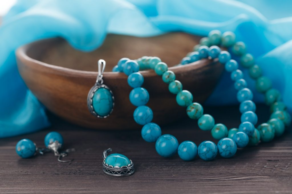 Handmade turquoise jewelry with earrings and necklaces on a table