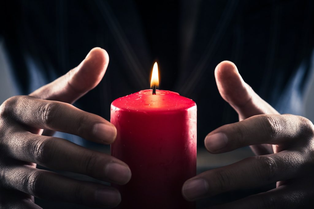 Practicing candle magic with hands placed around a burning red candle