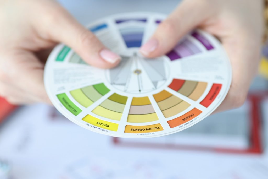 Hands holding color scheme tool used to find compatible and harmonious colors