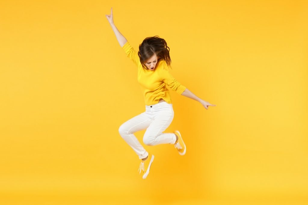 Happy woman in casual clothes jumping and spreading hands isolated on yellow background