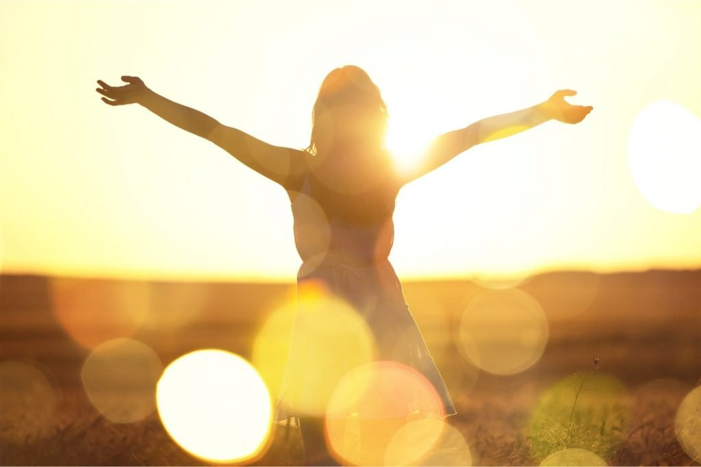 Happy woman filled with joy is celebrating the warm yellow colors of the sun