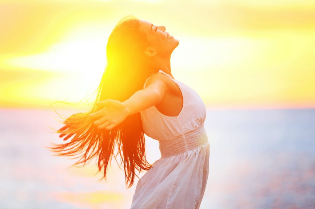 Happy woman in a white dress enjoying the sunrise with her arms outspread and face raised to the sky