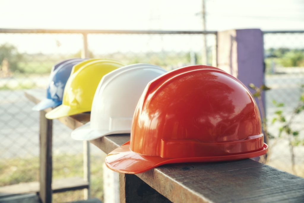 Hard hats with different color codes placed on wooden plank in construction site