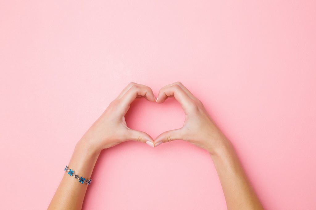 Heart shape created by woman's hands on a pink background