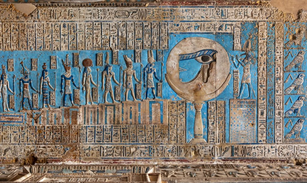 Hieroglyphic carvings and blue paint on the interior walls of an ancient Egyptian temple