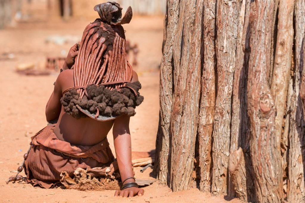 Himba tribal woman sitting outside her shack