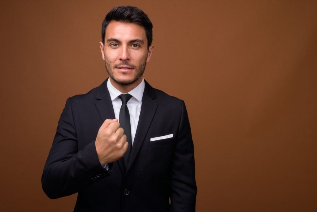 Studio shot of Hispanic businessman wearing a black suit against a brown background
