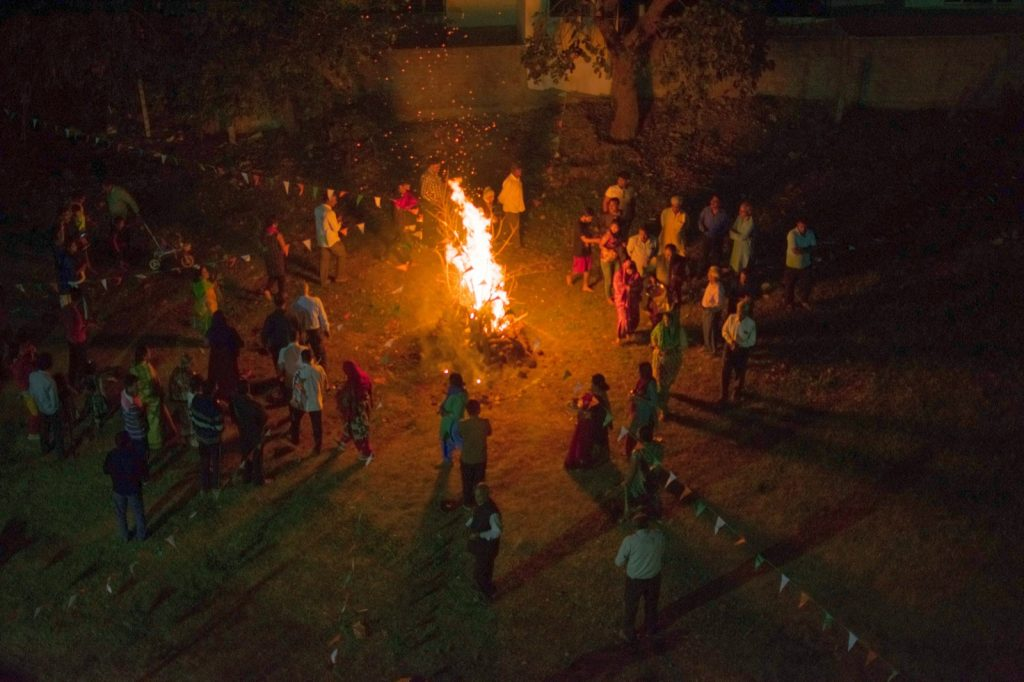 Holi celebration in India with people standing around pyre of fire