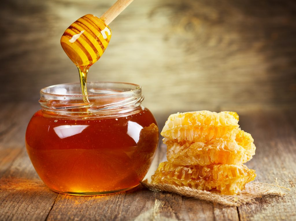 Glass jar of honey with honeycomb on the side standing on wooden table