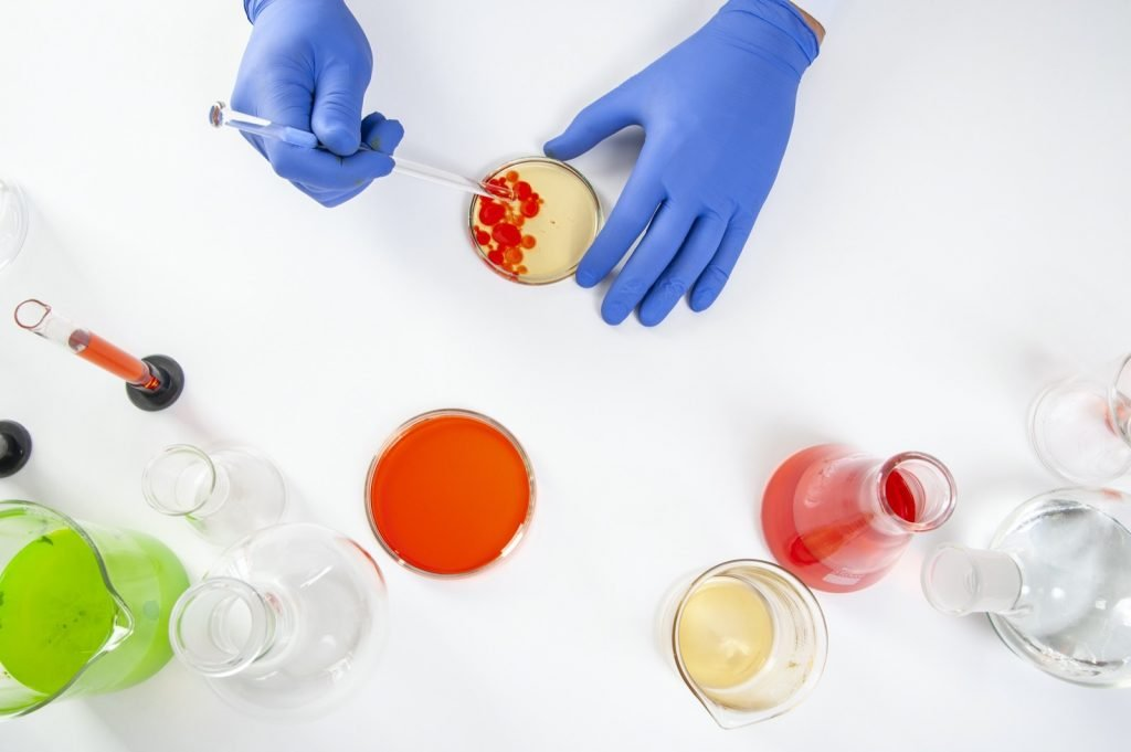Top view of human hands in laboratory performing color experiments