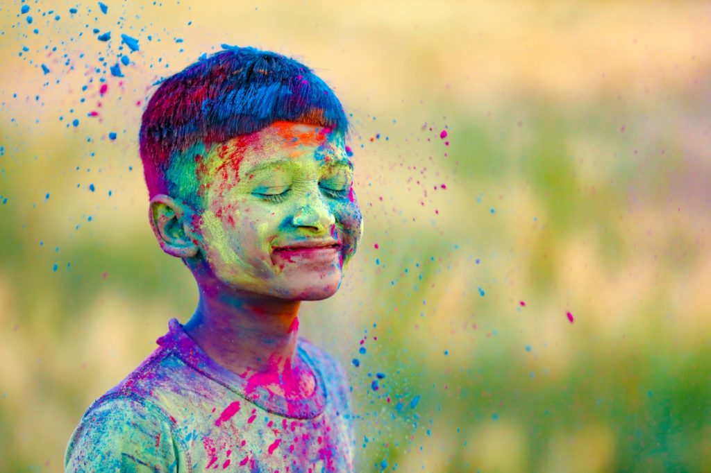 Smiling Indian child covered in color at Holi festival