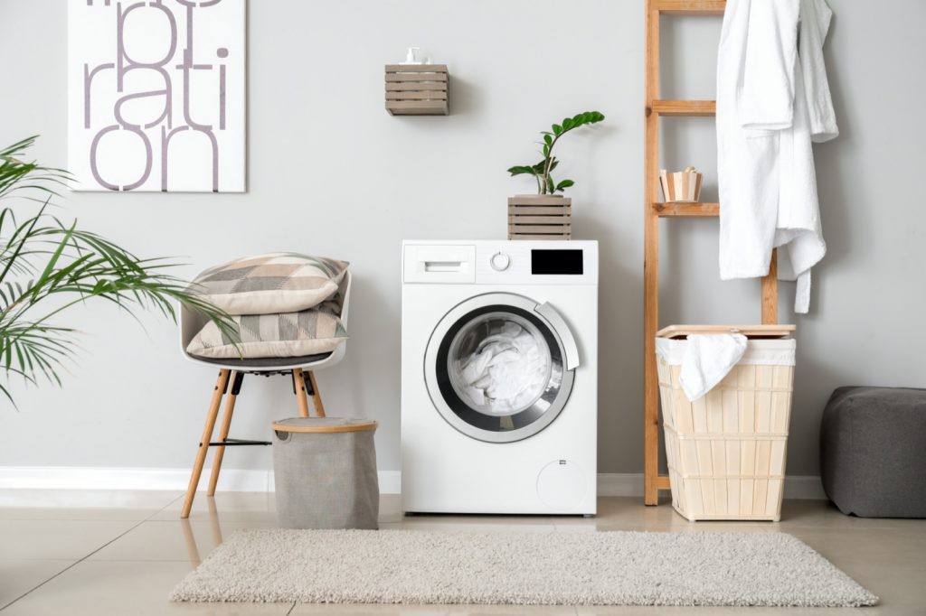 Interior of home laundry room with modern washing machine and gray painted walls