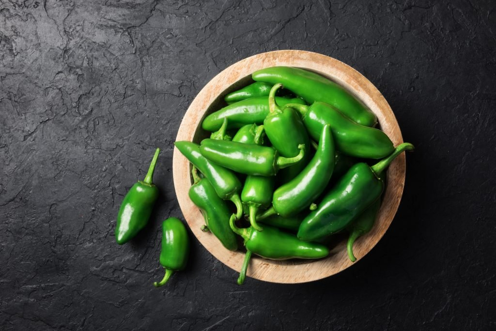 Green jalapeño peppers in a wooden bowle on black background