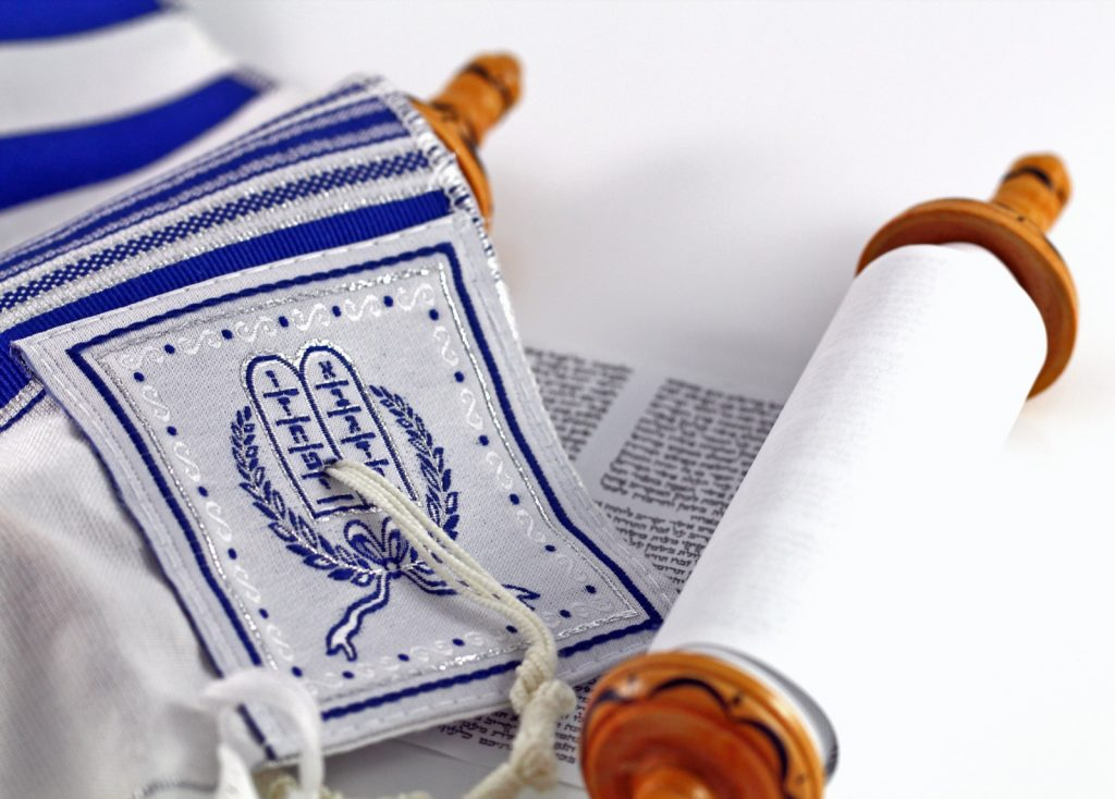 Traditional Jewish tallit prayer shawl with blue stripes over a Torah scroll
