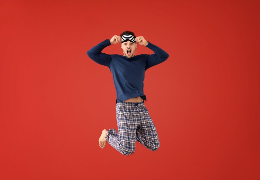 Jumping energetic man in pajamas with sleep mask on red background