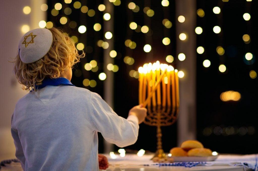 Kid celebrating Hanukkah and the Jewish Festival of Lights