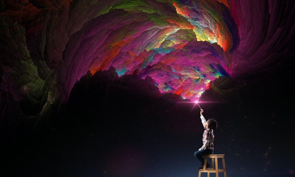 Dreaming kid waving a magic wand up in the air creating beautiful colors