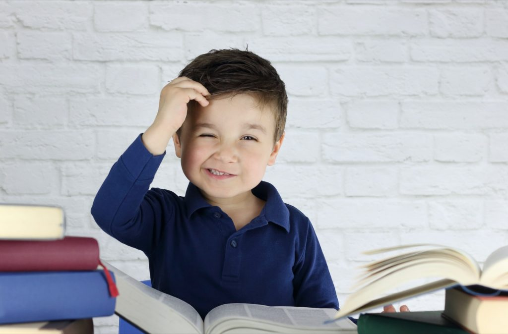 Kid surrounded by books scratching his head trying to learn how to read
