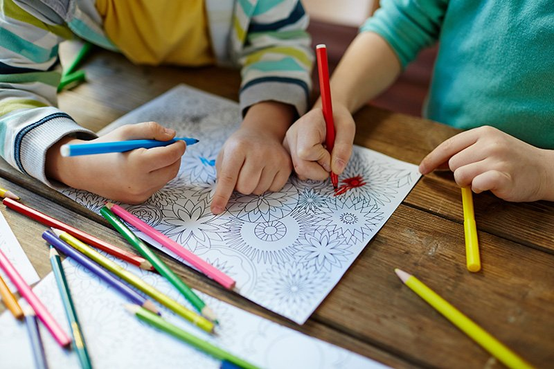 Kids coloring mandala with pencils of different colors