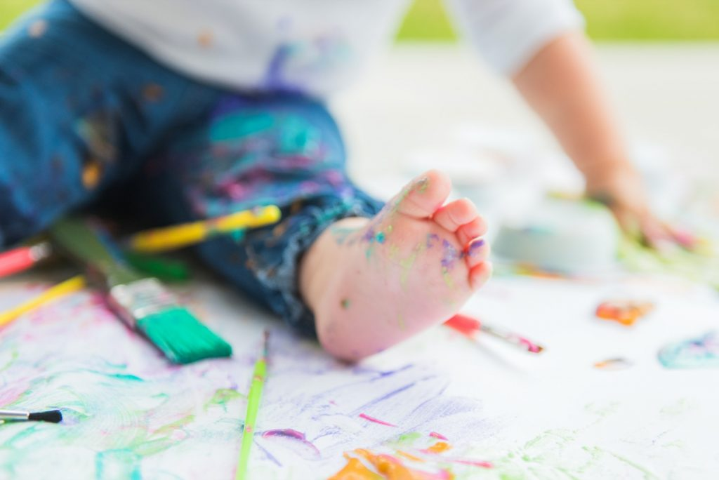 Kids foot with splattered paint colors and brushes and paint covered paper
