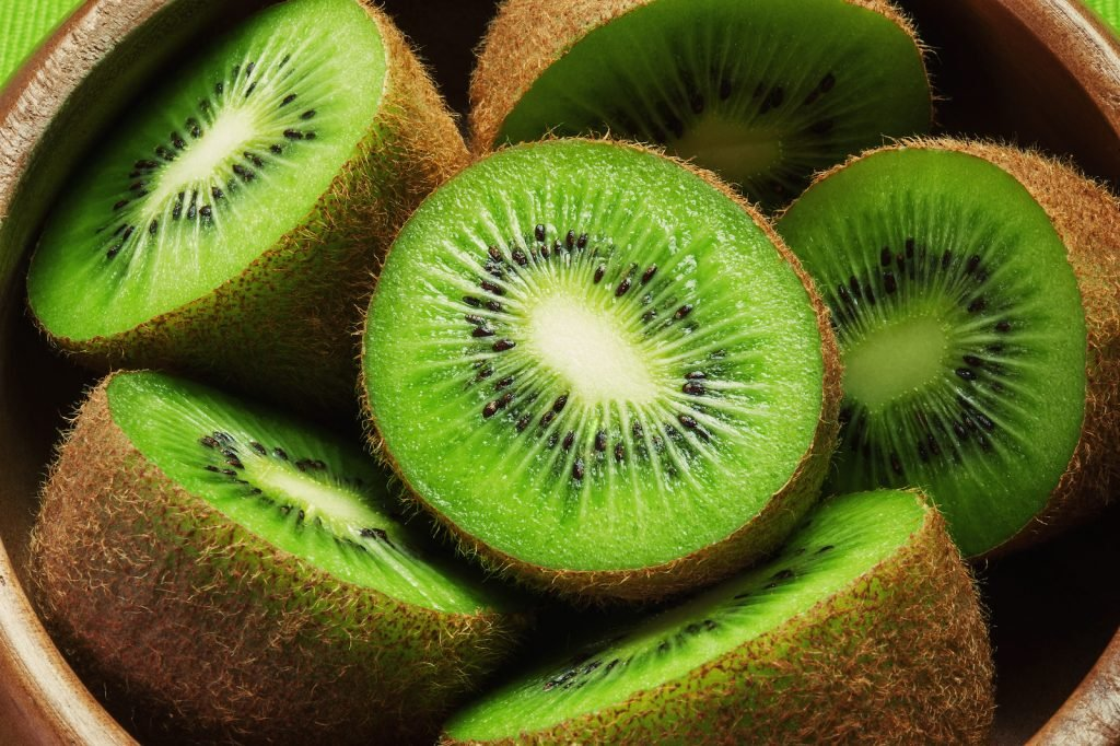 Top view of several half bright green kiwis in a wooden bowle