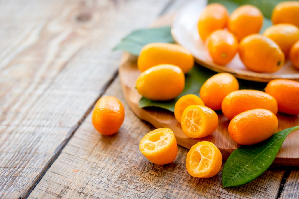 Bright Orange kumquat on a wooden plate standing on a wooden table
