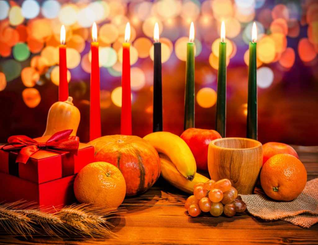 Kwanzaa holiday celebration with candles, gift box, pumpkin, wooden bowl and fruits
