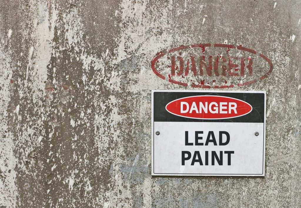 Lead paint danger warning sign on a white colored worn down wall