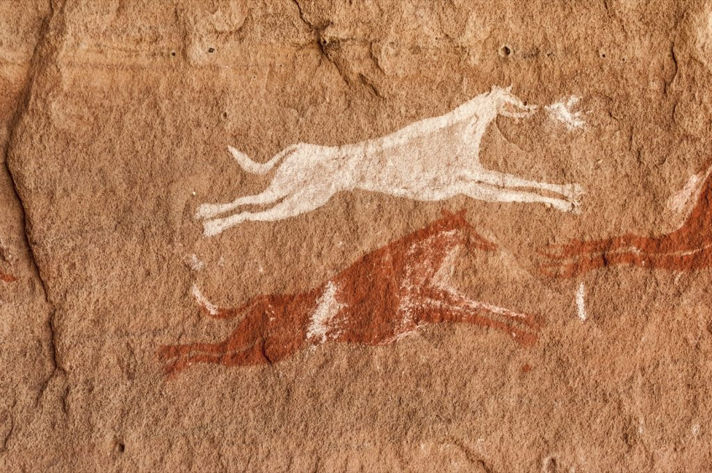 Libyan Sahara prehistoric white and red cave painting in the Acacus Mountains