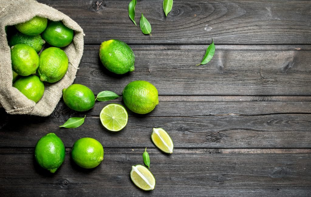 Fresh whole green limes in a linen bag spilling out onto a dark wooden background