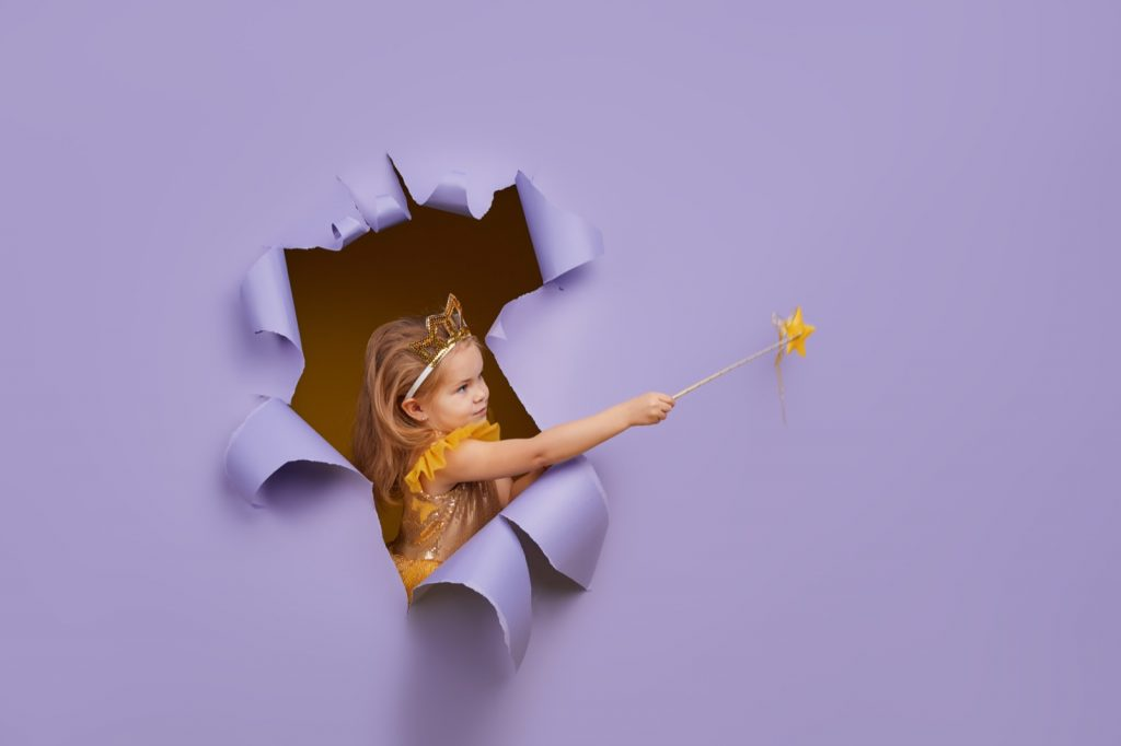 Little girl in princess costume breaks through a colored purple paper wall and points with a magic wand