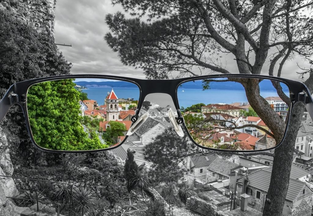 Looking through glasses to colorful view of old city center with red rooftops and blue sea surrounded by black and white background