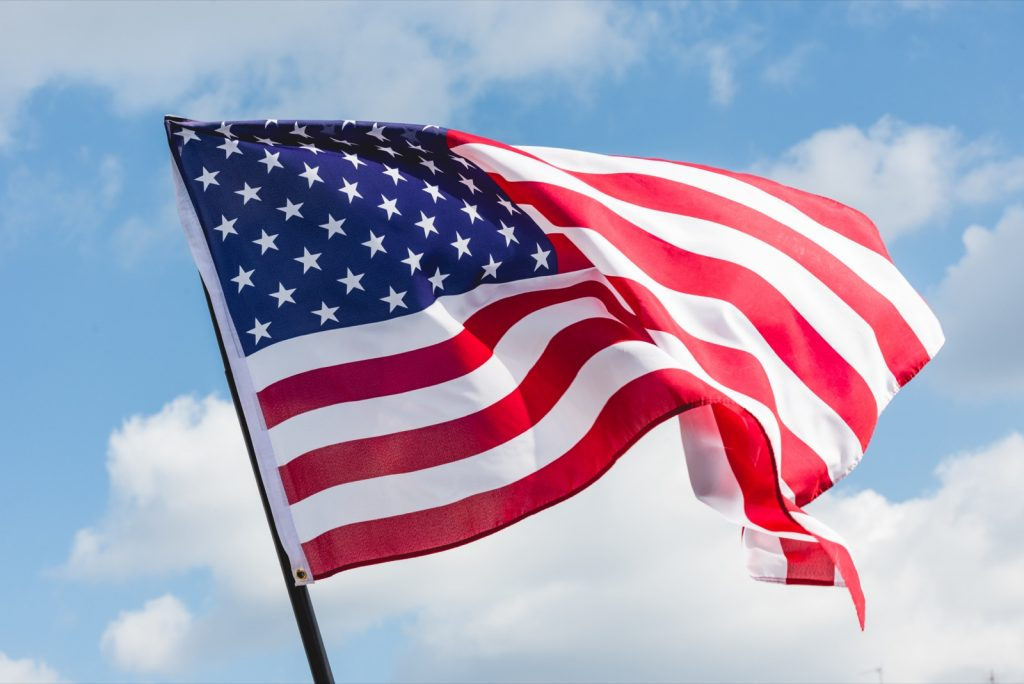 Low angle view of a colorful American flag against the blue sky