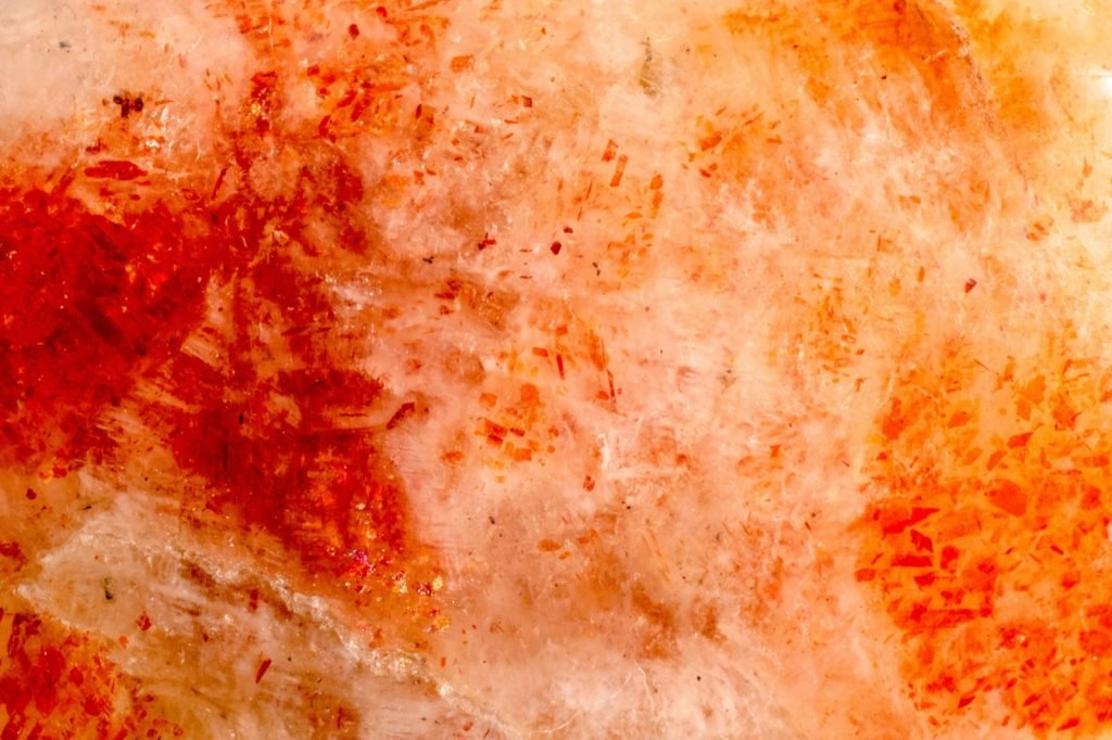 Macro photograph of polished sunstone in red and orange colors