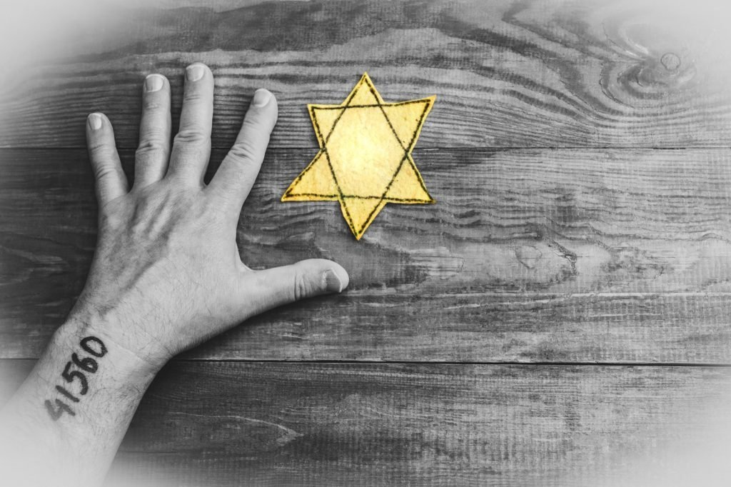 Male hand and yellow Jewish star of David on wooden board background