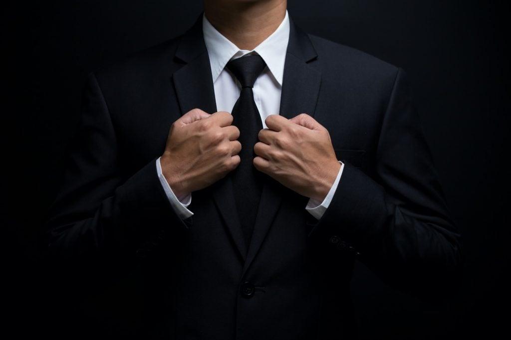 Man in black suit adjusting his black necktie