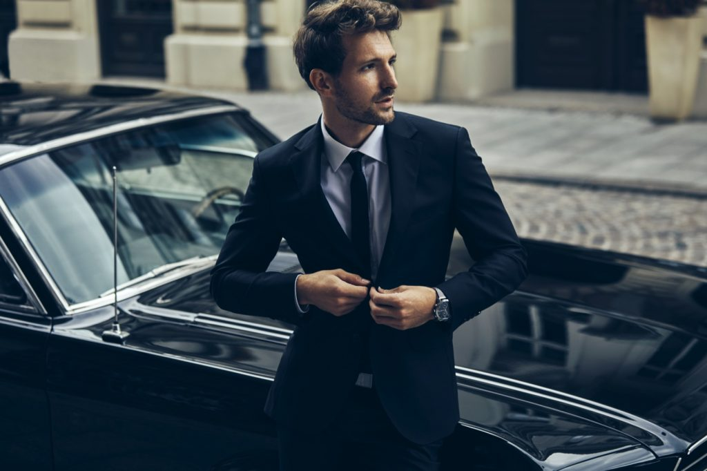 Man in black suit standing in front of old classic black car