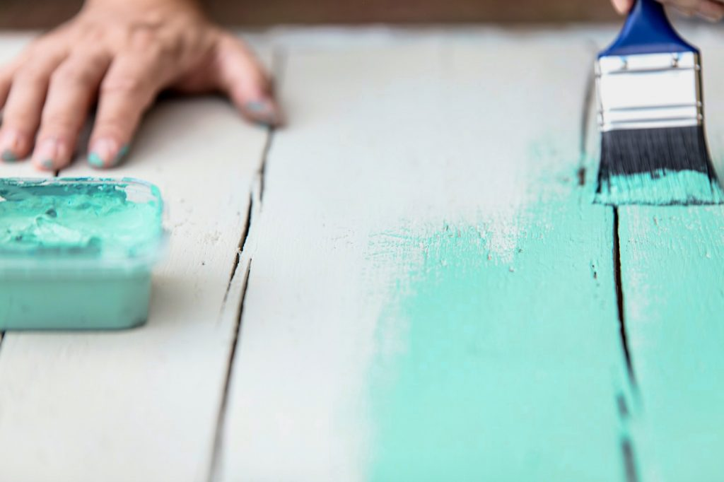 Man with a turquoise colored brush painting a wooden table