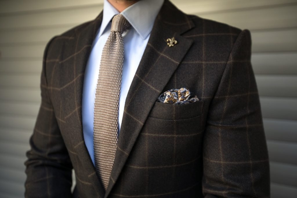Elegant tailored suit with brown tie