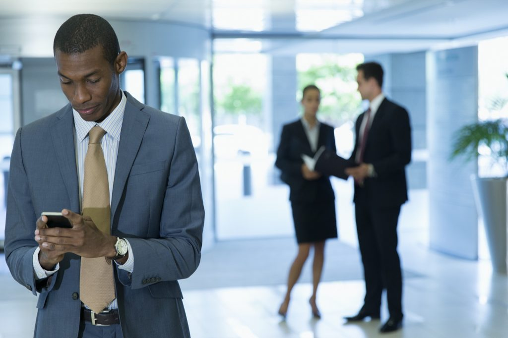 Man in grey suit looking at phone in office lobby after job interview